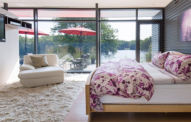 """The width of the cedar block """"wall"""" extending up through the master bedroom was designed to accommodate the homeowners' custom made, extra-wide 1950s bed."""