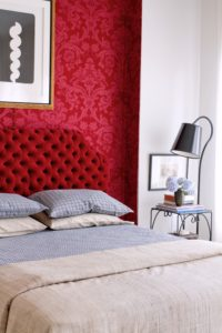 In the guestroom, splendid with a wall of crimson, Duralee damask, the French lamp/table dates from the 1960s. A mix of patterns and textures dress the bed.