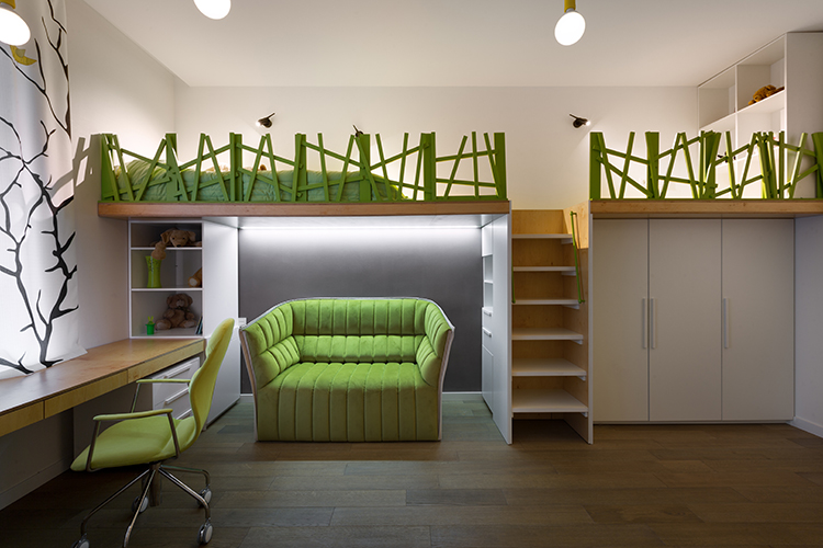 SOLUTIONS: For the teenage daughter, the designer created a stylish, multifunctional room with two beds, a work desk, and a comfortable, bright sofa. She went with a natural green, white and oak palette. BELOW: In the second room, intended for a boy, two beds are hidden under a wooden podium. A work desk placed near the window clears more space for fun and study. The white walls are decorated by blue and red wall art – a convenient way to dress up a child's room — delivering simplicity with a punch of character.
