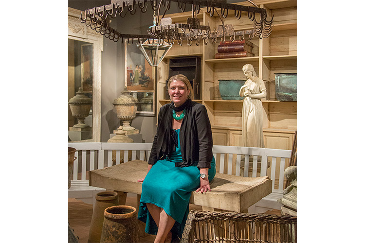Jennifer Quail seated beneath her favorite find of the day; a former gaming rack that could serve as a rustic chandelier at home or a pot rack in any modern day kitchen.