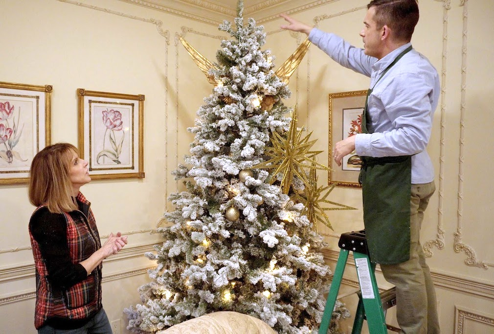 benjamin bradley decorating a white christmas tree with gold accents