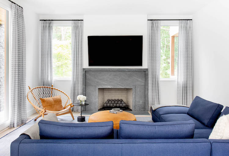 east hampton home lunge area with blue sectional and slate fireplace